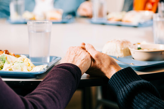 Seniors Holding Hands in Prayer Before a Meal