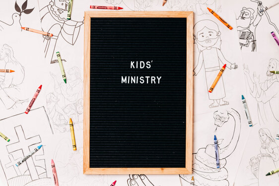 Kids' Ministry Letter Board Surrounded by Crayons and Coloring Pages