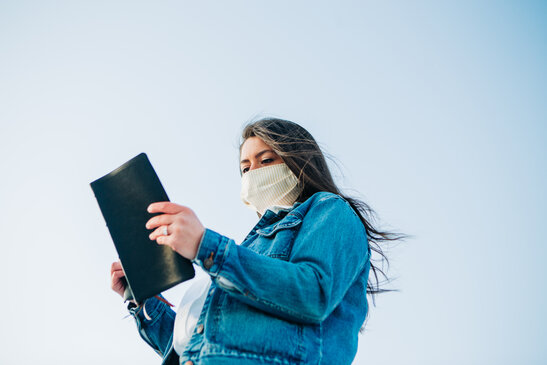 Woman Wearing a Face Mask and Reading the Bible