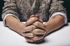 Praying hands of a senior woman