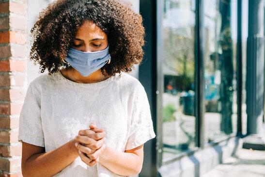 Woman Wearing a Mask and Praying