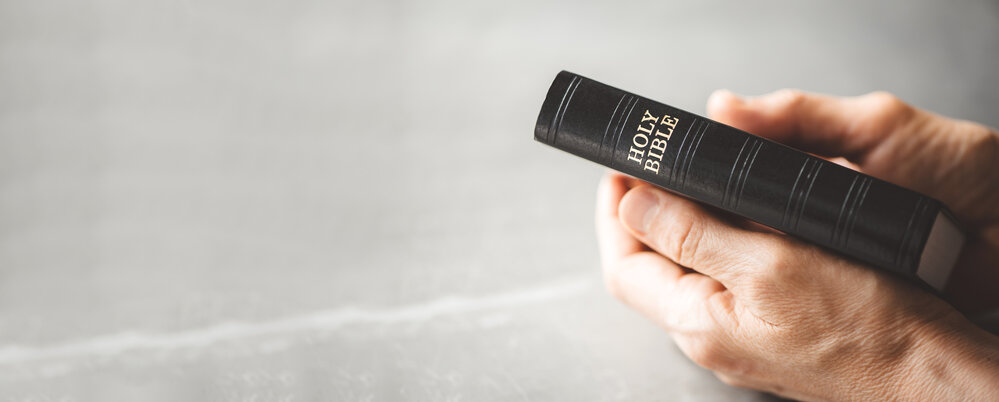Hands holding Holy Bible over grey background. Sharing the Gospel with youth. Copy space. Christian concept