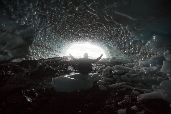 Man raising his hands in worship in an ice cave