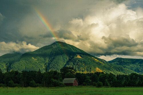 A rainbow over a green mountain