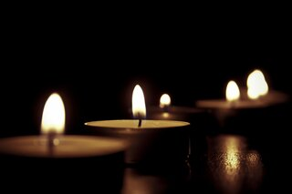 Tealight candles lit in a dark room.