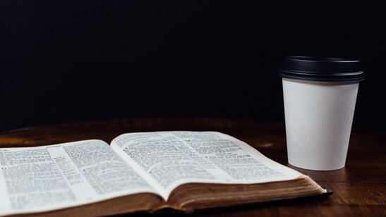 Coffee in to-go cup with open bible