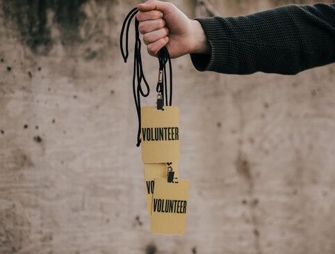 Hand in Frame Holding Volunteer Badges