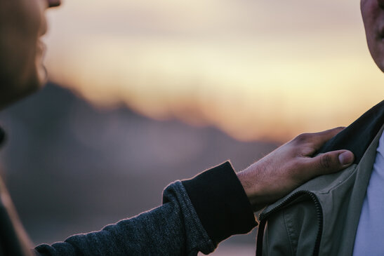 Man Putting Hand on Man's Shoulder