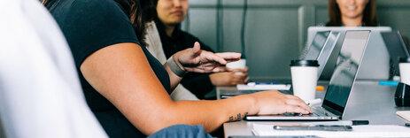 Woman Using Laptop During Meeting