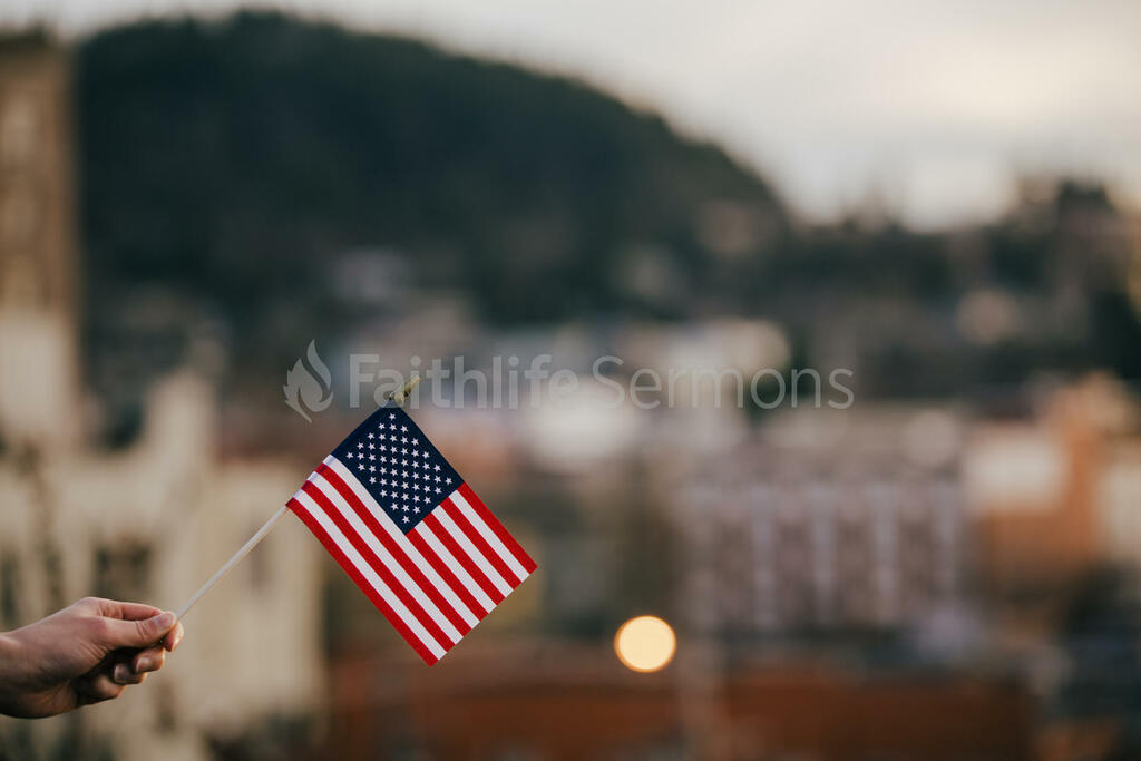 Patriotic Holidays hand in frame holding an american flag 16x9 55f18ea7 4622 4076 8c19 cee707c7a8e1 preview