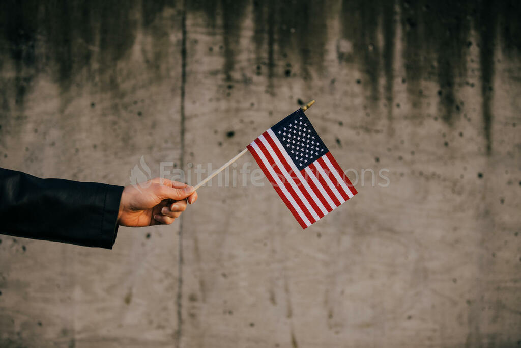 Patriotic Holidays hand in frame holding an american flag 16x9 72639cbf 3419 49db ab11 8acad75675ea preview