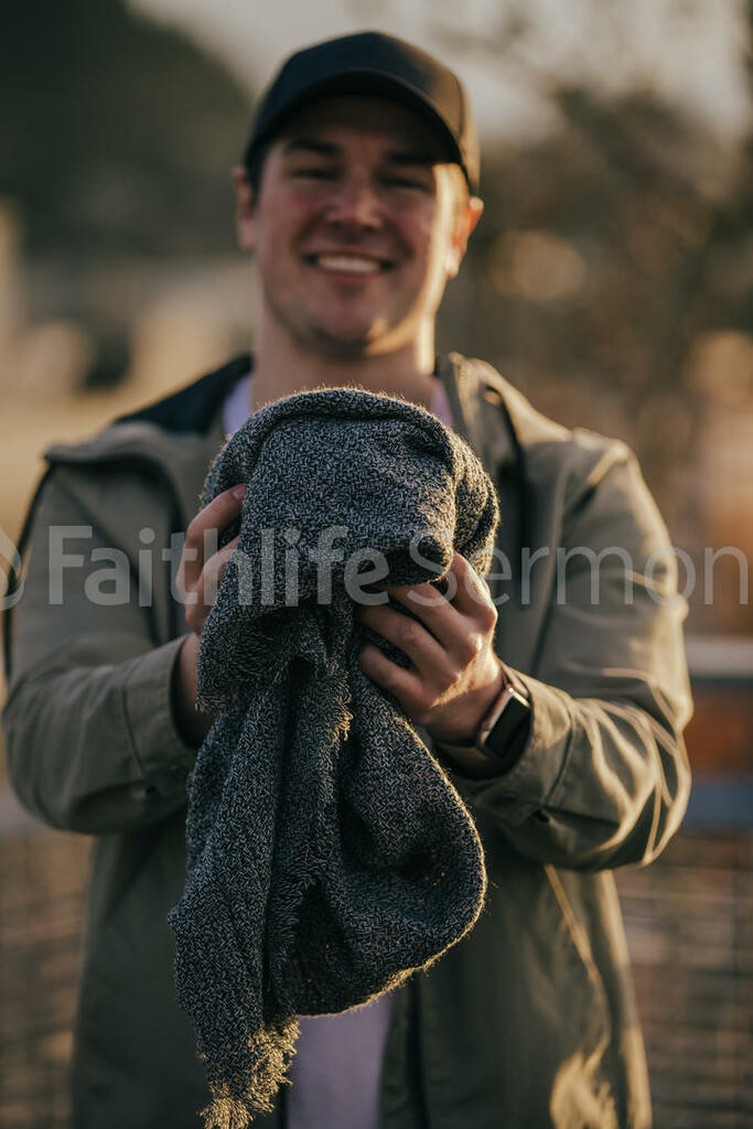 Clothing Drive man holding out a warm scarf 16x9 cb02702d ac32 400e b1b3 000aa9c9202f preview