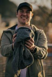 Clothing Drive man holding out a warm scarf 16x9 cb02702d ac32 400e b1b3 000aa9c9202f image