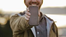 Technology man holding out a smart phone 16x9 f5868f18 b3b6 469d b50b cf3cca9406f7 PowerPoint image