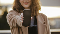 Technology woman holding out a smart phone 16x9 0c31ef74 6532 431f bc31 a0c7baf74cec PowerPoint image