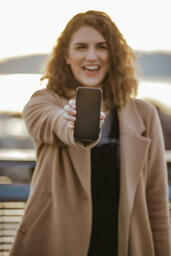 Technology woman holding out a smart phone 16x9 96e0427b a58a 4cf9 a139 af0167afd60f PowerPoint image