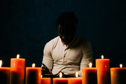 Man Reading Bible in Candle Lit Room  image 25