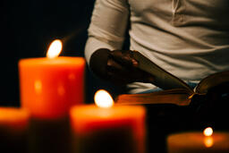 Man Reading Bible in Candle Lit Room  image 1
