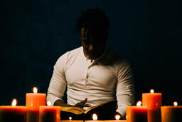 Man Reading Bible in Candle Lit Room  image 19