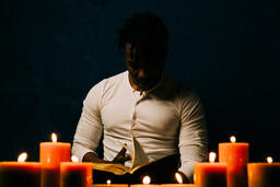 Man Reading Bible in Candle Lit Room  image 26