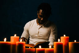Man Reading Bible in Candle Lit Room  image 4