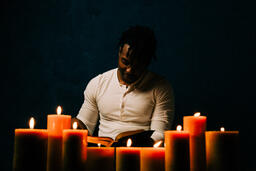Man Reading Bible in Candle Lit Room  image 28