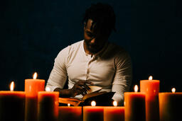 Man Reading Bible in Candle Lit Room  image 3