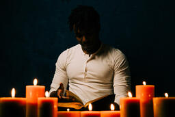 Man Reading Bible in Candle Lit Room  image 12