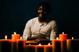 Man Reading Bible in Candle Lit Room  image 24