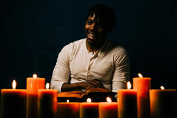 Man Reading Bible in Candle Lit Room  image 7