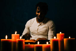 Man Reading Bible in Candle Lit Room  image 20
