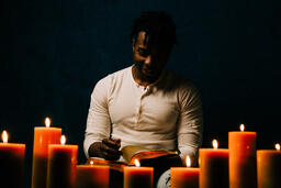 Man Reading Bible in Candle Lit Room  image 17