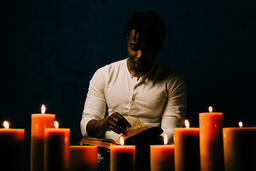 Man Reading Bible in Candle Lit Room  image 6