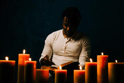 Man Reading Bible in Candle Lit Room  image 23