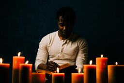 Man Reading Bible in Candle Lit Room  image 16