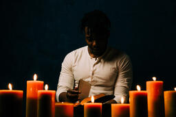 Man Reading Bible in Candle Lit Room  image 11