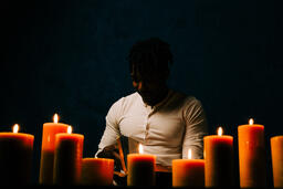 Man Reading Bible in Candle Lit Room  image 9