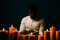 Man Reading Bible in Candle Lit Room  image 22