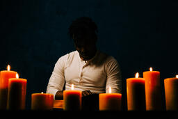 Man Reading Bible in Candle Lit Room  image 13