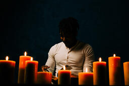Man Reading Bible in Candle Lit Room  image 10