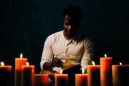 Man Reading Bible in Candle Lit Room  image 21