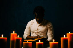 Man Reading Bible in Candle Lit Room  image 18