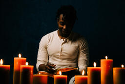 Man Reading Bible in Candle Lit Room  image 2