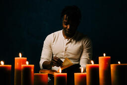 Man Reading Bible in Candle Lit Room  image 15