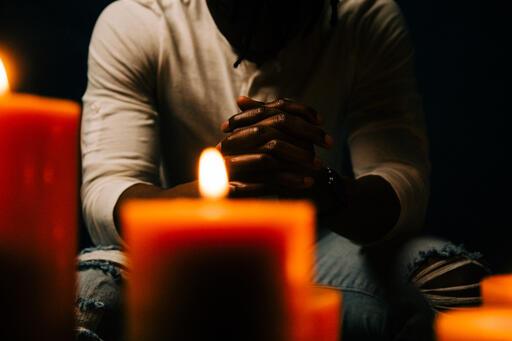 Man Praying in Candle Lit Room