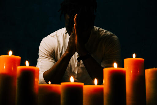 Man Praying in Candle Lit Room