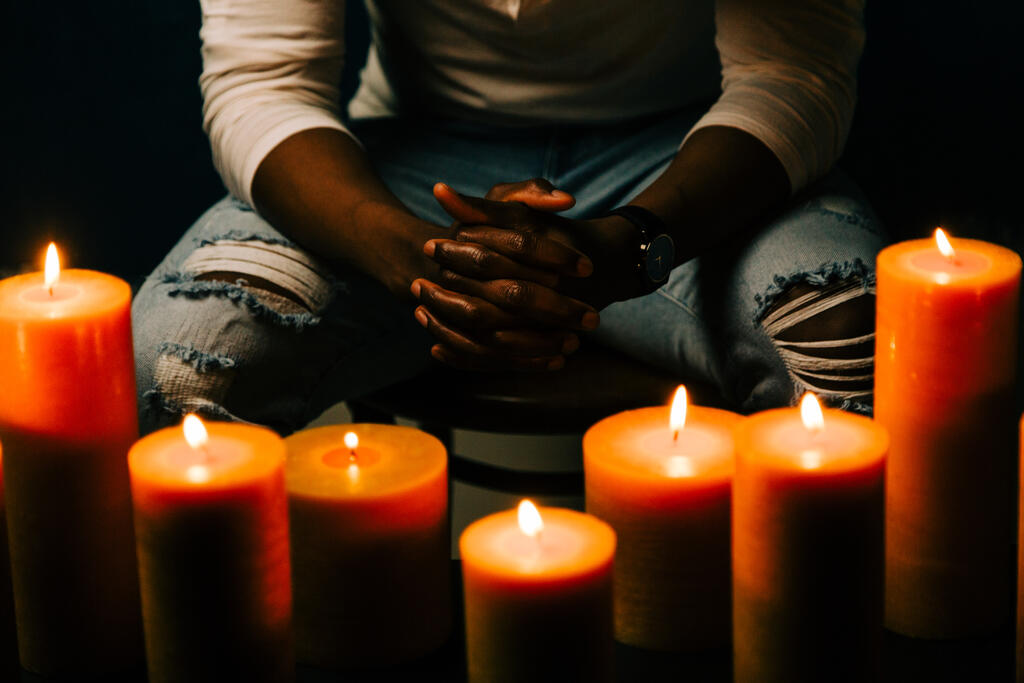 Man Praying in Candle Lit Room large preview