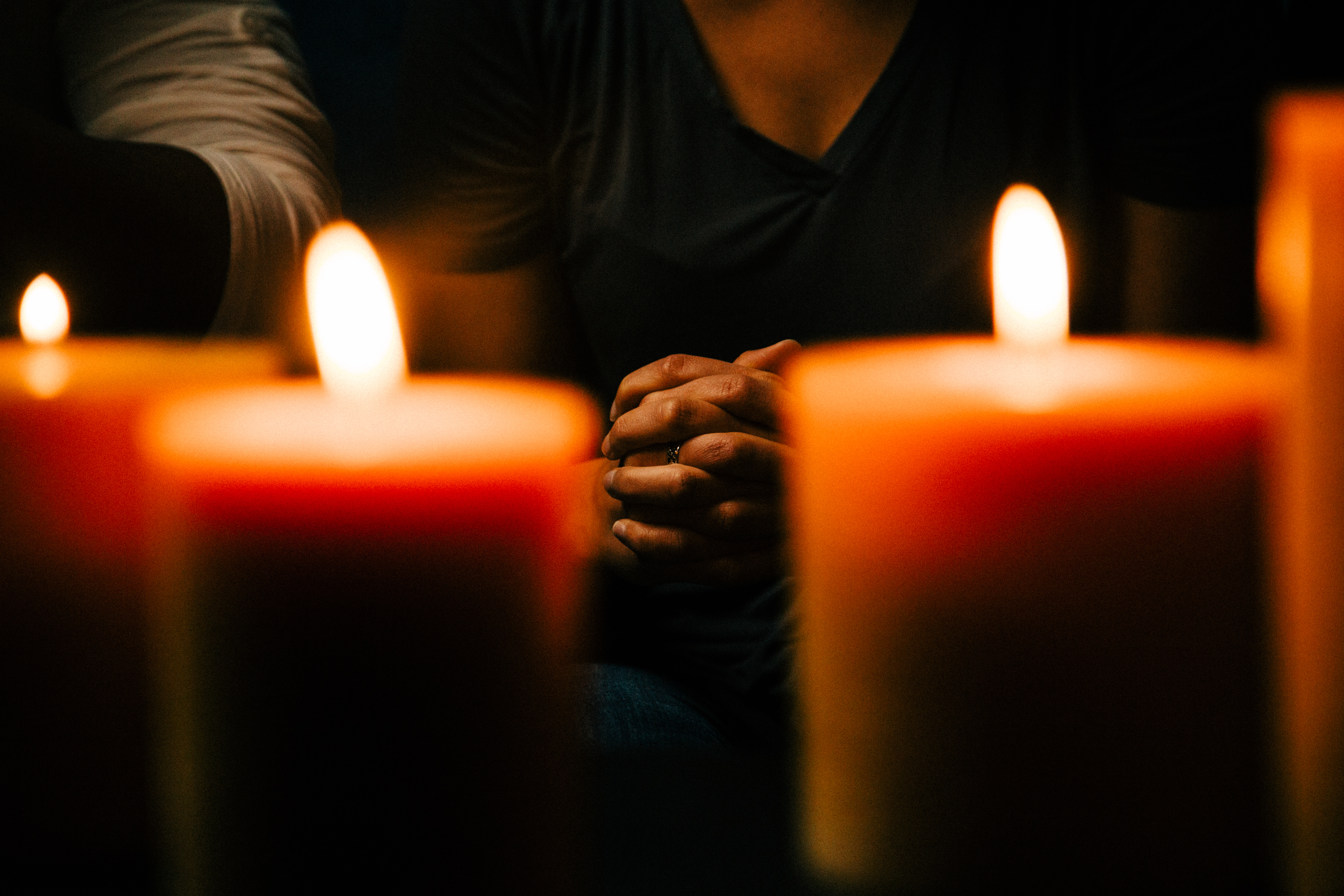 Woman Praying in Candle Lit Room