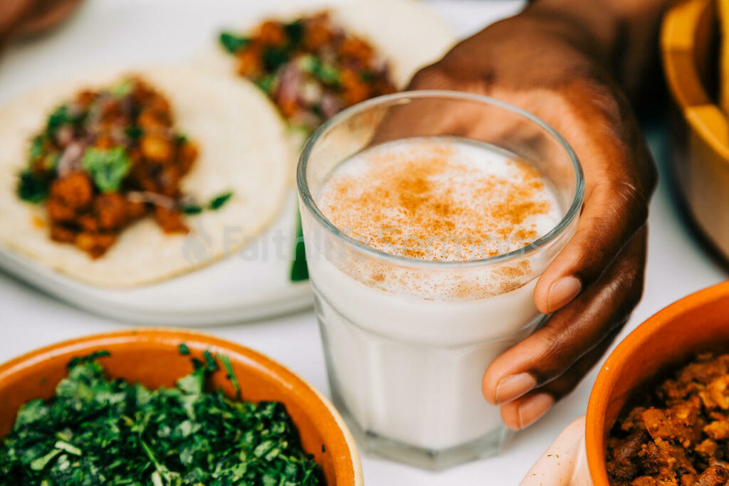 Mexican Food Spread hand holding cup of horchata 16x9 88c2124a 2a06 482f 9306 42bee69275f1 preview