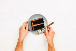 Cake hands holding plate with a slice of 16x9 84984cbd 170a 4b4e a239 21682e54aac0 image